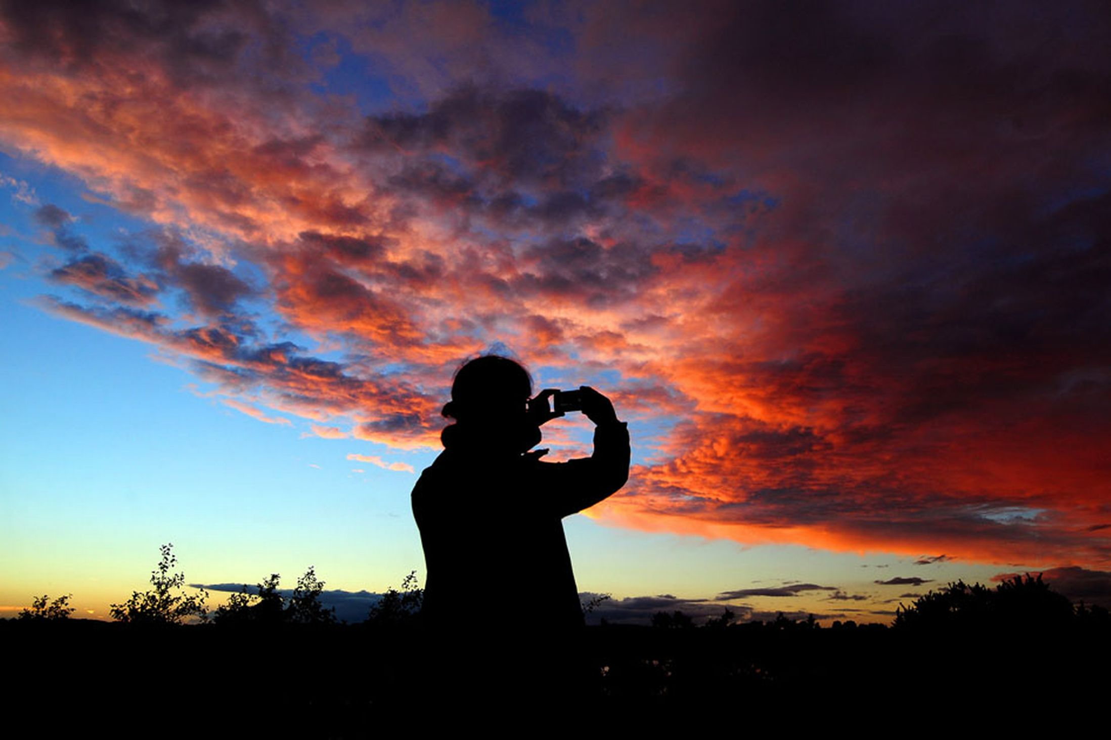 A-person-uses-a-phone-to-capture-a-sunset-sky-in-South-Derbyshire-19t-October-2641176