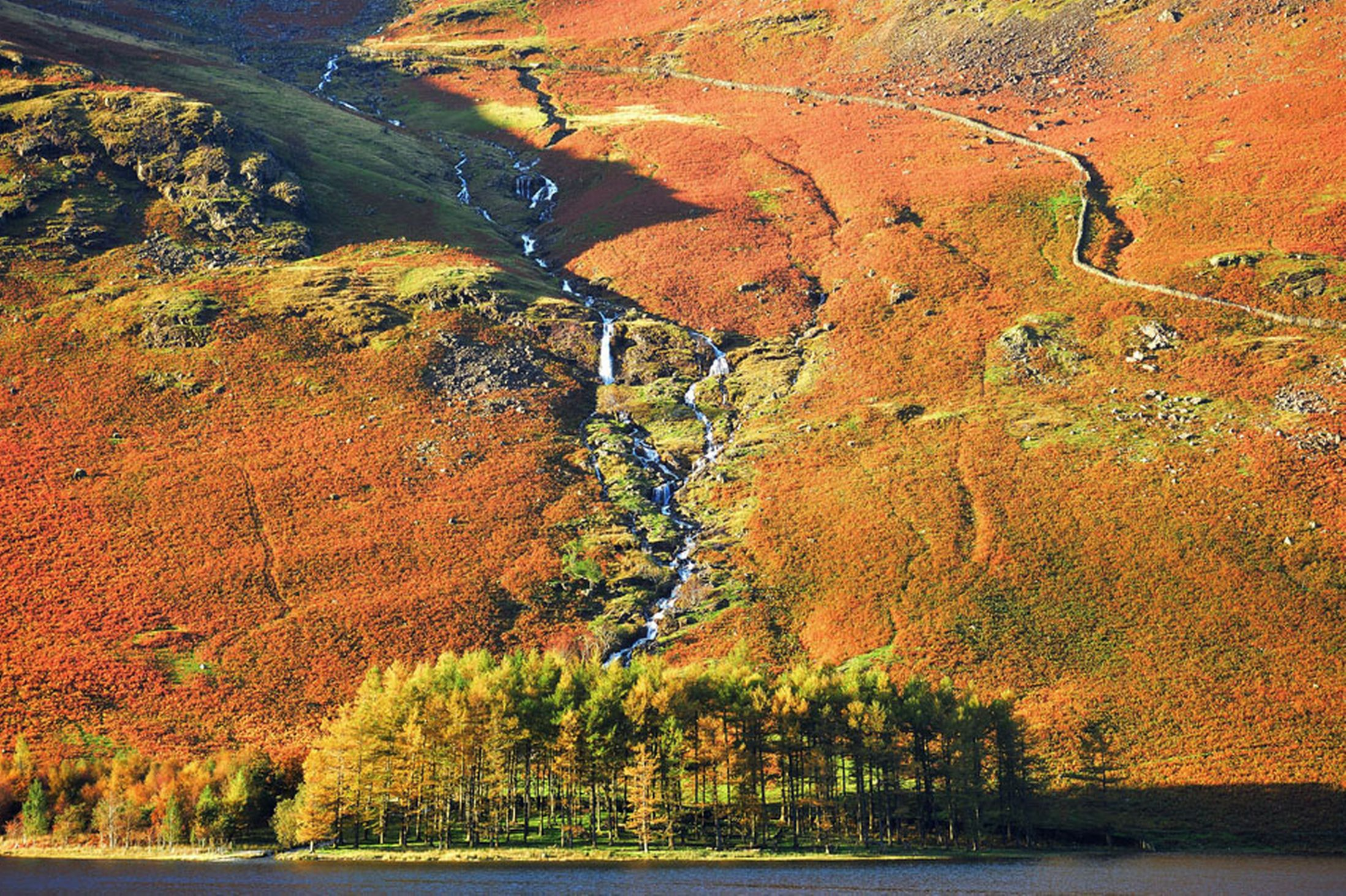 A-waterfall-flows-into-lake-Buttermere-in-Cumbria-24th-October-2641165