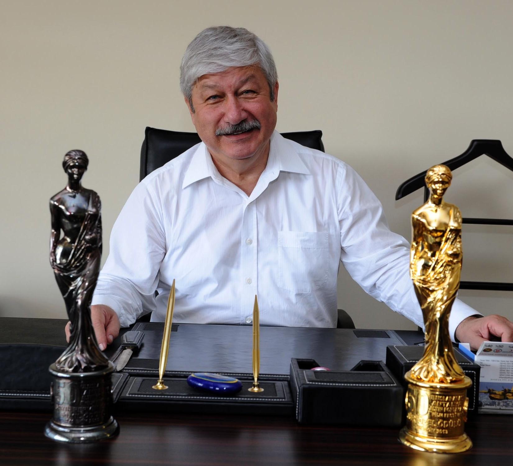 Mustafa Akaydın'ın önündeki Altın Portakal'lardan soldaki Antalya'da verilen ilk ödül, sağdaki ise sonuncusu...